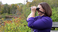 woman holding binoculars to her eyes
