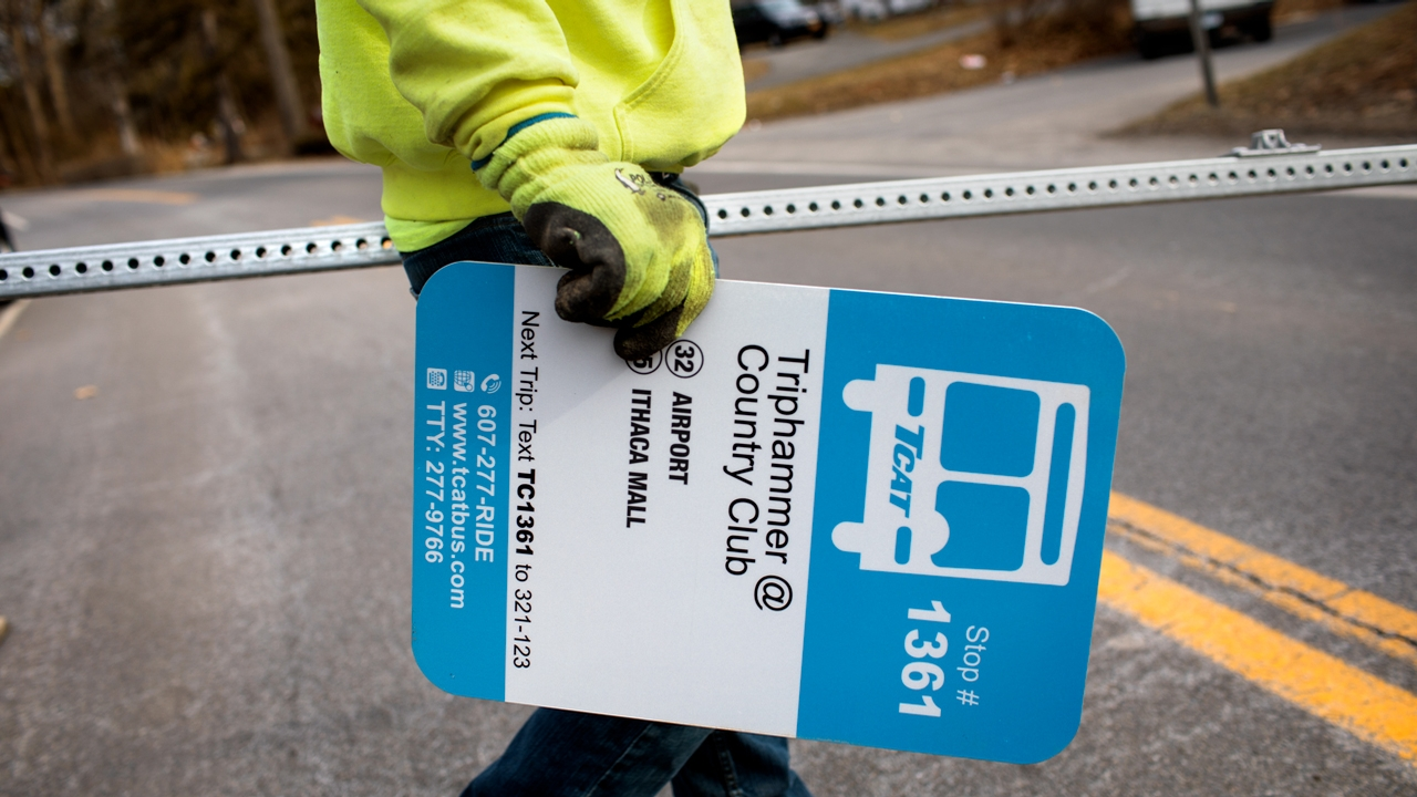 A contractor prepares to install a new TCAT bus stop sign in Cayuga Heights.