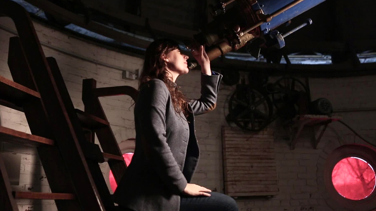 Lisa Kaltenegger looking through a telescope