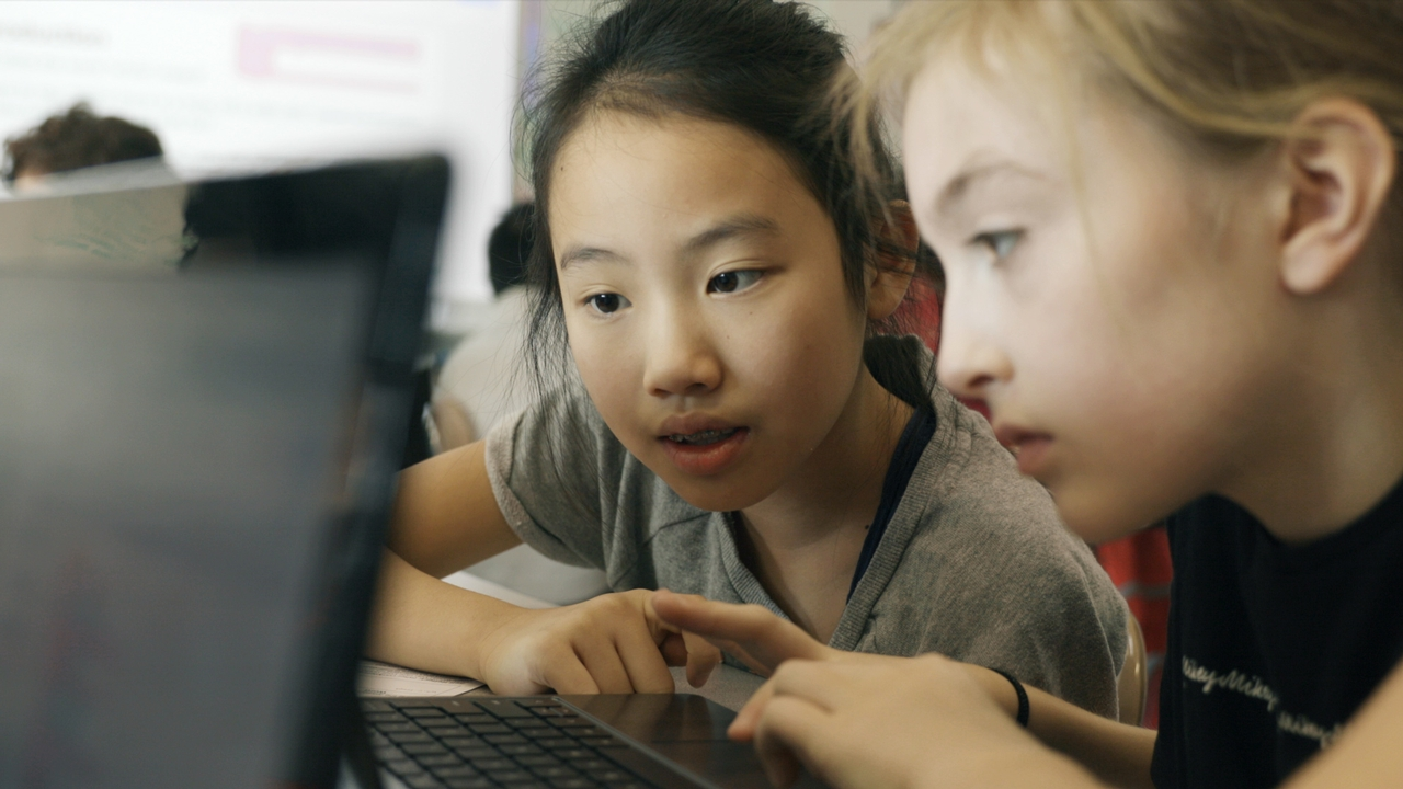 Two children using a computer.