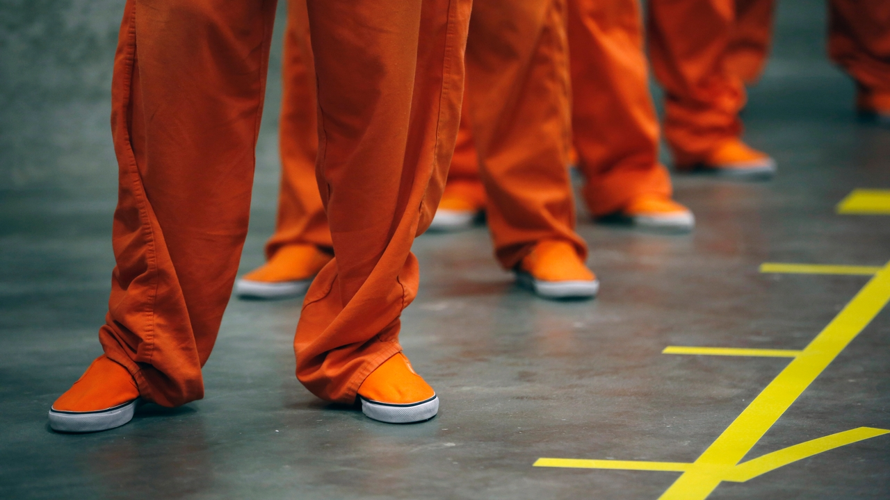inmates in orange jumpsuits
