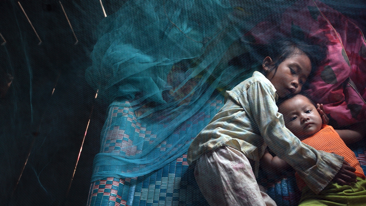 Cambodian children under a mosquito bed net