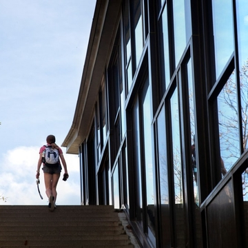 A student walks beside Noyes Hall on West Campus.
