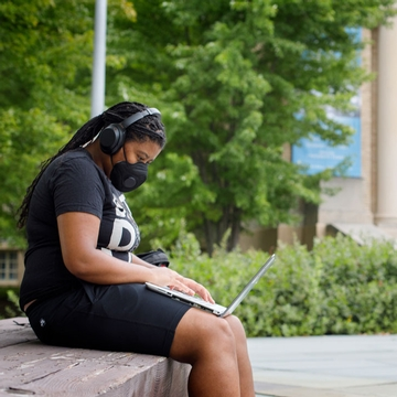A Cornell student sits on a bench in front of Bailey Hall