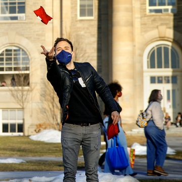 A student throws a red beanie bag towards the camera on the Arts Quad.