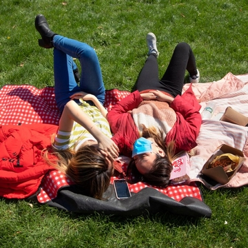 Two students lay on a red blanket on the Arts Quad during Big Red Pride Days