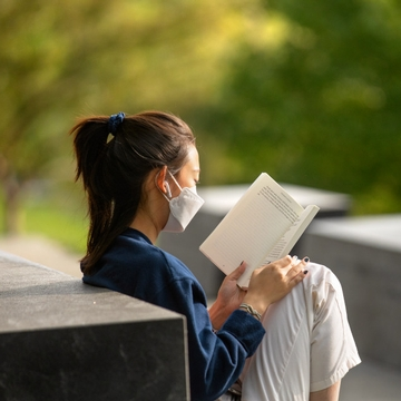 a student reads a book in front of libe slope at Cornell University