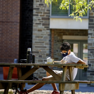 A student reads outside at a picnic table