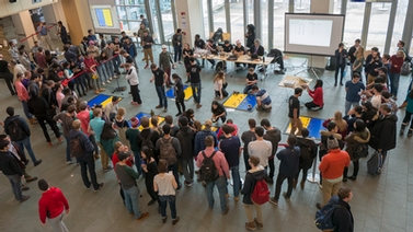 a crowd of people gathered around several floor mats with robots being demonstrated