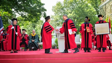 Martha Pollack and Robert Harrison shake hands during the installation ceremony