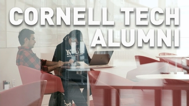 Alumni sit at a table working on laptops