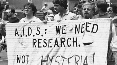 people hold banner that reads AIDS: We Need Research, Not Hysteria