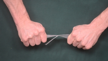 hands pulling apart a piece of plastic