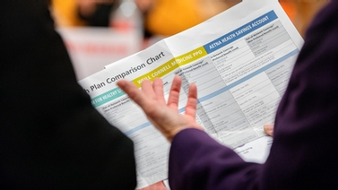 Closeup of person holding benefits plan comparison chart.