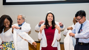 new medical students don white coats