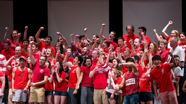 Alumni and students sing together on stage at Bailey Hall