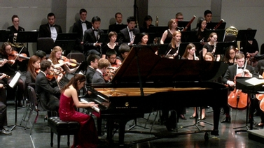 woman at grand piano with background orchestra