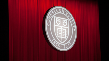 Cornell seal on red curtain