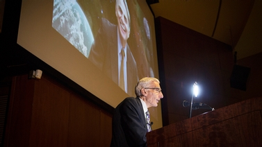 Lord Martin Rees at the podium, with photo of Carl Sagan in background