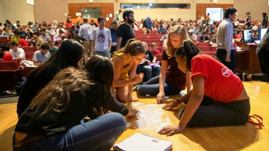 group of students examines index cards laid out on the floor