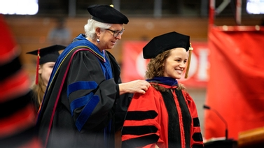 Barbara Knuth with graduate student onstage in Barton Hall.