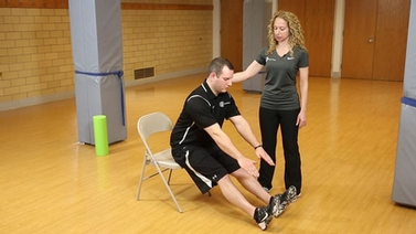 Kerry and TJ, exercise physiologists from Cornell Wellness, demonstrate a stretch