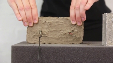 hands holding a block of dirt