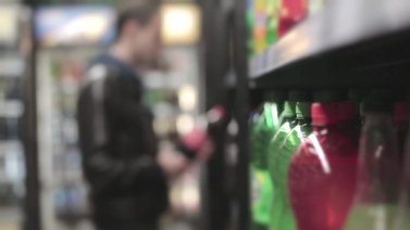 Man takes a bottle of soda off of the shelf in a convenience store