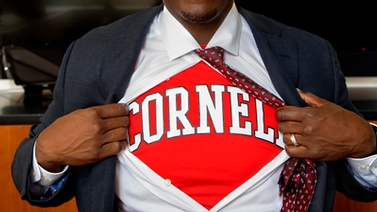 Kevin Boothe pulls open his button down shirt to reveal a red Cornell shirt underneath