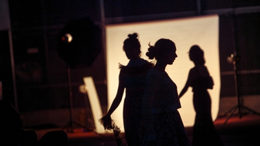 Three women in silhouette backstage.