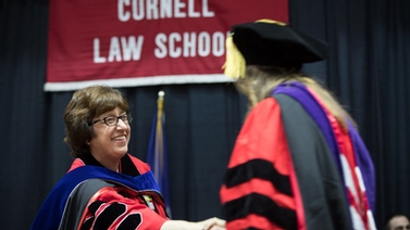 President Pollack shakes the hand of a Law School graduate