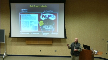 Dr. Joseph J. Wakshlag stands near a projector screen showing an Alpo pet food label