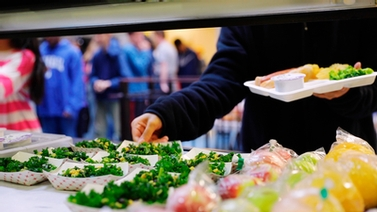 student chooses leafy greens in the cafeteria line