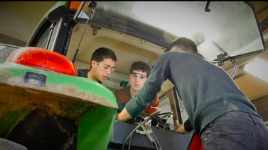 students work on the tractor in the shop