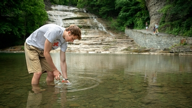 member of Ruth Richarson's lab takes a water sample