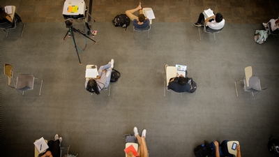Students sit at distanced desks in a classroom at Cornell University