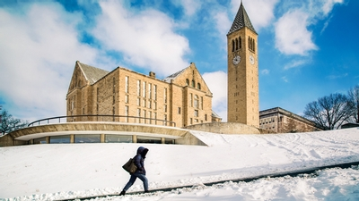 A students walks up a snow-covered Libe Slope at Cornell University