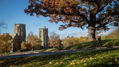 A person walks on Libe Slope with Cornell Law School in the background.
