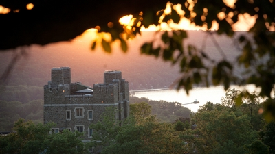 an orange sunsets through branches over Cayuga Lake at Cornell University