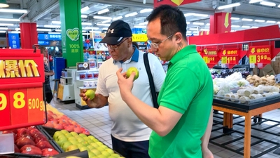 Jinzhou (Joel) Li, vice president of Qimei, foreground, and Ralph Christy, inspect apples at a Chine