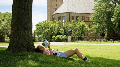 a female student sits under a tree on the Arts Quad at Cornell University