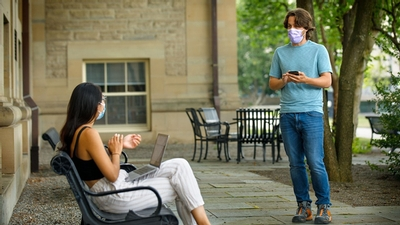 Bryan Maley, a graduate student in the Master of Public Health program, surveys a student on campus about her experiences wearing a mask.