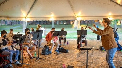 James Spinazzola leads students during rehearsal under a tent on the Arts Quad for his Wind Symphony class.