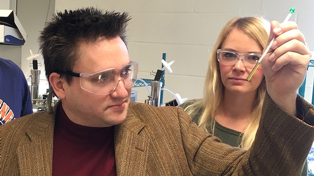 Kyle Lancaster and Avery Vilbert examine a thin vial of cytochrome P460