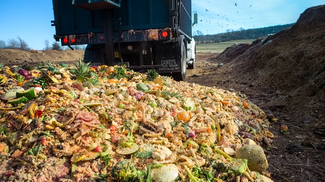 truck unloads a pile of food waste