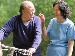 smiling older couple goes for a bike ride