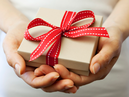 a small box with red ribbon held by two hands